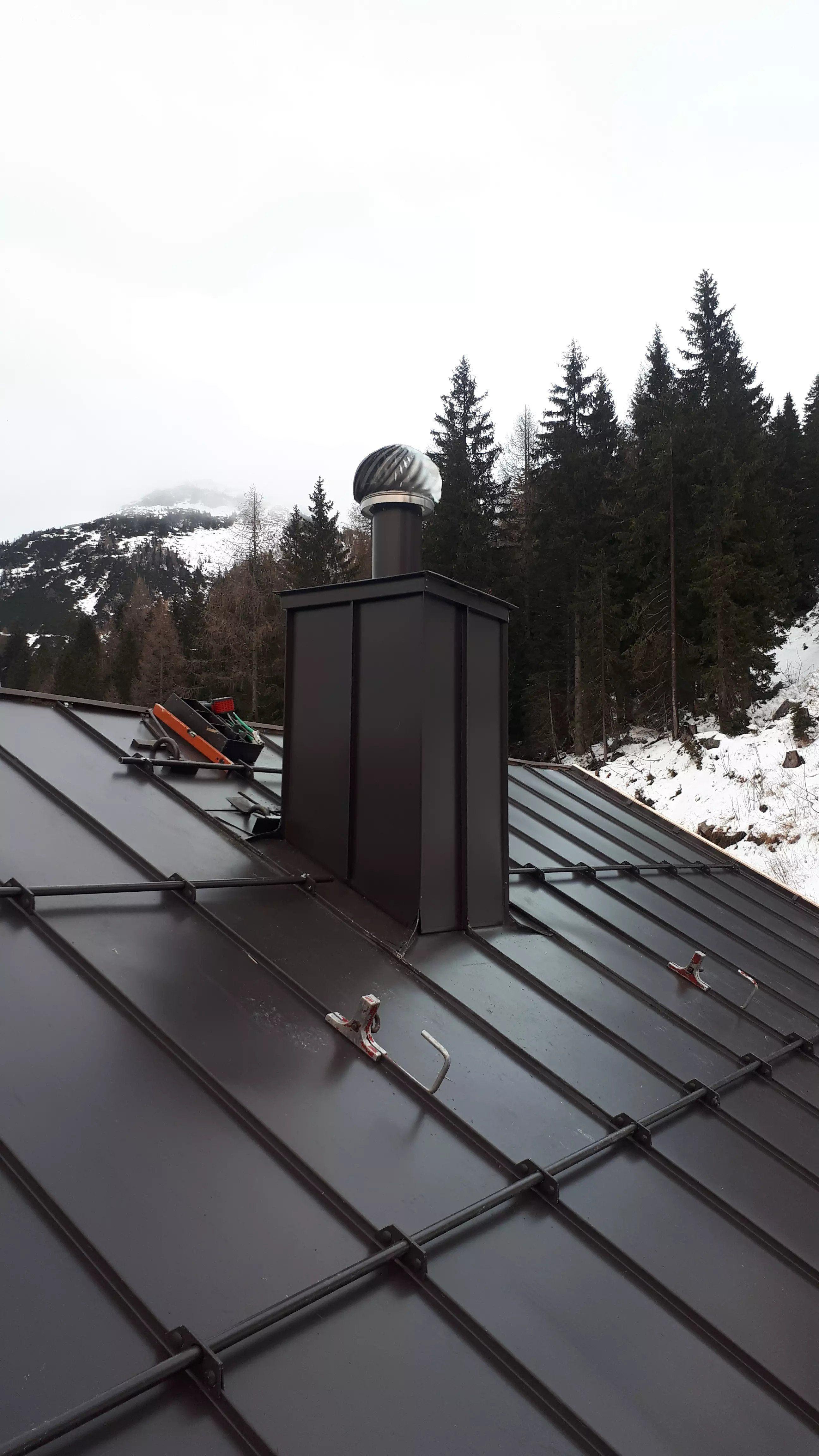 Dacheindeckung und Kamin Almhotel